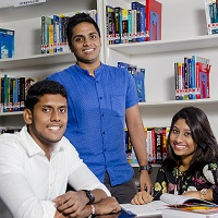 Three students at table in library
